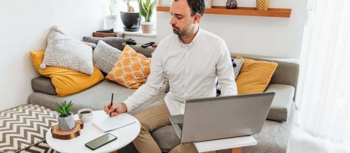 man-sitting-on-couch-in-living-room-working-on-laptop-computer-home-office-working-working-from-home_t20_xXJ0lQ